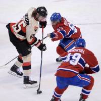 Photo - Ottawa Senators defenceman Erik Karlsson attempts to get the puck past Montreal Canadiens defenseman Francis Bouillon and forward Michael Bournival during second period NHL hockey action in Ottawa on Friday, April 4, 2014.  (AP Photo/The Canadian Press, Sean Kilpatrick)