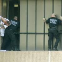 Photo - JUMPER, JUMP: Local attorney Robert Behlen struggles with sheriff's tactical team members on the ledge before falling from the OU Medical Center near NE 10th and Lincoln in Oklahoma City, Okla. Sept. 27, 2007.  BY STEVE GOOCH, THE OKLAHOMAN  ORG XMIT: KOD