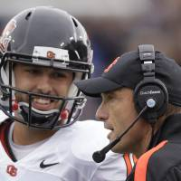 Photo - Oregon State coach Mike Riley, show here talking with quarterback Cody Vaz,will try to pull off the upset Saturday at Stanford. (AP Photo/Rick Bowmer)  Rick Bowmer - AP