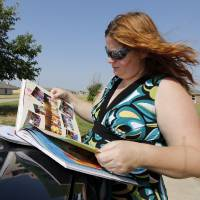 Photo -  Lora Trammell shows photos of her son, Porter, in a Plaza Towers Elementary School yearbook. Porter survived the May 20, 2013, tornado at the school but was not allowed to attend the school this year because their house hasn't been rebuilt. The school is visible in the background. Photo by Steve Sisney, The Oklahoman   STEVE SISNEY -