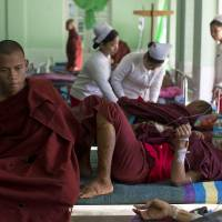 Photo - Buddhist monks with burn injuries are treated at a hospital in Monywa, northwestern Myanmar, Thursday, Nov. 29, 2012. Security forces cracked down on protesters occupying a copper mine early Thursday, using water cannons and other devices to break up the rally hours before opposition leader Aung San Suu Kyi was expected to hear their grievances. Unexplained fires engulfed the protest camps at the Letpadaung mine in northwestern Myanmar and dozens of Buddhist monks and villagers were injured, according to several protesters. (AP Photo/Gemunu Amarasinghe)