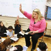 Photo - Teacher Kristin Whitmore works on a reading assignment with her third-graders from the book