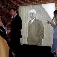Photo - A crowd, including John E. Kirkpatrick's grandson Chris K. Keesee, at left, pass by a newly unveiled portrait of John E. Kirkpatrick.  PHOTO BY BRYAN TERRY, THE OKLAHOMAN
