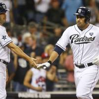 Photo - San Diego Padres' Carlos Quentin, right, is congratulated by Seth Smith after his two-run home run against the Cincinnati Reds in the seventh inning of a baseball game Tuesday, July 1, 2014, in San Diego. (AP Photo/Lenny Ignelzi)
