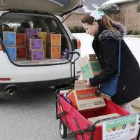 Photo - Girl Scout Katie Francis moves boxes back into the car after selling cookies in a neighborhood Wednesday, February 5, 2014. Photo by Doug Hoke, The Oklahoman
