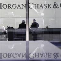 Photo - FILE - In this May 11, 2012 file photo, people stand in the lobby of JPMorgan Chase headquarters in New York. JPMorgan Chase reported a 55 percent jump in earnings for the last three months of 2012 as mortgage fees and other income surged. (AP Photo/Mark Lennihan, File)