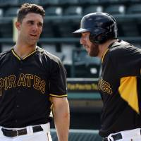 Photo - Pittsburgh Pirates' Brent Morel, right, talks with Andrew Lambo as he warms up before taking batting practice before the team's annual spring training Black and Gold intra-squad baseball game in Bradenton, Fla., Tuesday, Feb. 25, 2014. The Pirates will start Grapefruit League play Wednesday against the New York Yankees in Bradenton. Morel, acquired Monday from the Toronto Blue Jays, did not play in the game. (AP Photo/Gene J. Puskar)
