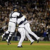 Photo -   From left, Detroit Tigers' Gerald Laird, Phil Coke and Jhonny Peralta celebrate after winning Game 4 of the American League championship series 8-1, against the New York Yankees, Thursday, Oct. 18, 2012, in Detroit. The Tigers move on to the World Series. (AP Photo/Paul Sancya )
