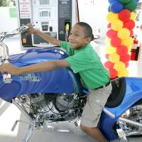 Photo - Kamari Morgan, 9, poses for a photo on The Chesapeake CNG Chopper in 2009 during the opening of an OnCue Expess CNG filling station at 4920 N Western in Oklahoma City .  Photo by Steve Gooch, The Oklahoman Archives  Steve Gooch -  The Oklahoman