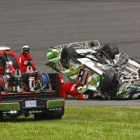 Photo - Track officials check on the condition of Kyle Busch, still in the car, after he flipped over in a multi-car crash during the NASCAR Sprint cup Series auto race at Daytona International Speedway in Daytona Beach, Fla., Sunday, July 6, 2014. (AP Photo/Ron Sanders)