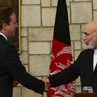Photo - Afghan President Hamid Karzai, right, shakes hands with British Prime Minister David Cameron during a press conference at the presidential palace in Kabul, Afghanistan, Saturday, June 29, 2013. Karzai urged Taliban militants to sit down at the negotiating table, saying Saturday his government is still willing to start peace talks with the insurgents despite an attack by the group on the presidential palace this week. (AP Photo/Massoud Hossaini, Pool)