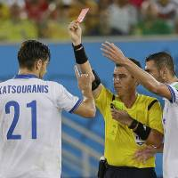 Photo - Referee Joel Aguilar from El Salvador shows a red card to Greece's Kostas Katsouranis, left, during the group C World Cup soccer match between Japan and Greece at the Arena das Dunas in Natal, Brazil, Thursday, June 19, 2014.  (AP Photo/Ricardo Mazalan)