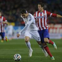 Photo - Atletico's Javi Manquillo, bottom, commits a foul on Real's Cristiano Ronaldo, front, during a semi final, 2nd leg, Copa del Rey soccer match between Atletico de Madrid and Real Madrid at the Vicente Calderon stadium in Madrid, Spain, Tuesday, Feb. 11, 2014. (AP Photo/Andres Kudacki)