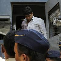 Photo - One of four men convicted of gang raping a photojournalist  in India's financial capital of Mumbai last year stands inside a police van as he is brought to prison, in Mumbai, India, Thursday, March 20, 2013. The Mumbai court is expected to sentence the men on Friday, said Maharashtra state Home Minister R.R. Patil. The four face a minimum of 20 years in prison, and could receive life sentences, said Prosecutor Ujjwal Nikam. (AP Photo/Rajanish Kakade)