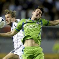 Photo -   Los Angeles Galaxy's David Beckham, left, battles Seattle Sounders' Brad Evans for the ball during the first half of an MLS Western Conference finals soccer game, Sunday, Nov. 11, 2012, in Carson, Calif. (AP Photo/Chris Carlson)