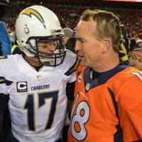 Photo - San Diego Chargers quarterback Philip Rivers, left, and Denver Broncos quarterback Peyton Manning greet each other at midfield after the Broncos beat the Chargers 24-17 in an NFL AFC division playoff football game, Sunday, Jan. 12, 2014, in Denver. (AP Photo/Jack Dempsey)