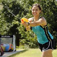Photo -  Volunteer Taylor Cannon plays water games with children at Camp ClapHans, an outreach program of the J.D. McCarty Center in Norman. PHOTO BY STEVE SISNEY, THE OKLAHOMAN   STEVE SISNEY -