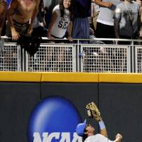 Photo - UCLA outfielder Christoph Bono catches a fly ball hit by North Carolina State's Trea Turner to end the eighth inning of an NCAA College World Series baseball game in Omaha, Neb., Tuesday, June 18, 2013. (AP Photo/Eric Francis)