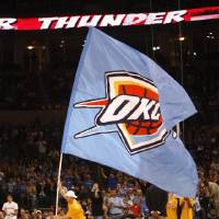 Photo - FIRST REGULAR SEASON WIN: An Oklahoma City Thunder flag is carried onto the court during a break in the action of an NBA basketball game between the Thunder and the Minnesota Timberwolves in Oklahoma City, Sunday, Nov. 2, 2008. Oklahoma City won 88-85. (AP Photo/Sue Ogrocki) ORG XMIT: OKSO108