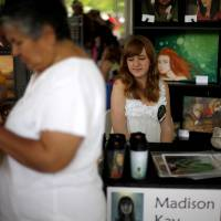 Photo - Madison Kay, 15, sits at her booth during the first Youth Art Sale at the Oklahoma Festival of the Arts in Oklahoma City, Saturday, April 28, 2012. Photo by Bryan Terry, The Oklahoman