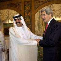 Photo - U.S. Secretary of State John Kerry, right, is greeted by Qatari Emir Hamad bin Khalifa Al Thani at Wajbah Palace in Doha, Qatar, on Sunday, June 23, 2013. In Qatar Kerry spent time discussing Syria and Afghanistan. The meeting is the last event in Qatar before Kerry heads to India. (AP Photo/Jacquelyn Martin, Pool)
