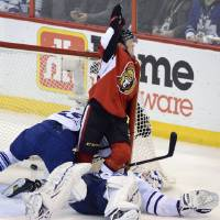 Photo - Ottawa Senators' Erik Condra, center, celebrates his goal as Toronto Maple Leafs goaltender Ben Scrivens, right, lies on his back and Korbinian Holzer falls into the net during the second period of an NHL hockey game in Ottawa, Ontario, on Saturday, Feb. 23, 2013. (AP Photo/The Canadian Press, Sean Kilpatrick)