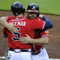 Photo - Atlanta Braves' Evan Gattis, right, is hugged by teammate Freddie Freeman (5) after hitting a three-run home run against the Los Angeles Angels to also score Freeman and Jason Heyward during the first inning of a baseball game on Friday, June 13, 2014, in Atlanta. (AP Photo/David Tulis)