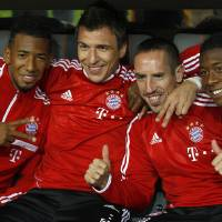 Photo - Munich's Jerome Boateng, from left, Mario Mandzukic of Croatia, Franck Ribery of France and David Alaba of Austria pose for media  prior to the German soccer cup second round match between FC Bayern Munich and Hannover 96, in Munich, southern Germany, Wednesday, Sept. 25, 2013. (AP Photo/Kerstin Joensson)