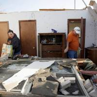 Photo - Pam and Terry Nelson sort through items inside the Woodward home of his mother, Wilma Nelson, after a tornado hit the house Sunday. Wilma Nelson also survived a tornado in Woodward in 1947. Photo by Bryan Terry  BRYAN TERRY - THE OKLAHOMAN