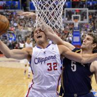 Photo - Los Angeles Clippers forward Blake Griffin, left, shoots as New Orleans Pelicans center Jeff Withey defends during the first half of an NBA basketball game, Saturday, March 1, 2014, in Los Angeles. (AP Photo/Mark J. Terrill)