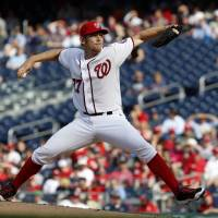 Photo - Washington Nationals starting pitcher Stephen Strasburg throws during the fourth inning of a baseball game against the Miami Marlins at Nationals Park on Thursday, April 10, 2014, in Washington. (AP Photo/Alex Brandon)