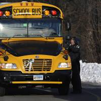 Photo - A police officer greets a bus at the entrance to a school on the first day of classes after the holiday break, in Newtown, Conn., Wednesday, Jan. 2, 2013. Nearly three weeks after the shooting rampage at Sandy Hook Elementary School in Newtown, students and teachers from the school will return to class Thursday in the neighboring town of Monroe. (AP Photo/Jessica Hill)