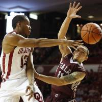 Oklahoma's Jordan Woodard (10) passes the ball past UALR's Devonte Smith (11) during a mens basketball game between OU and UALR at Lloyd Noble Center in Norman, Okla., Friday, Nov. 29, 2013.  Photo by Garett Fisbeck, For The Oklahoman