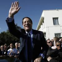 Photo - Right-wing opposition leader and presidential candidate Nicos Anastasiades waves to his supporters after voting in the Presidential election in southern port city of Limassol, Cyprus, Sunday, Feb. 17, 2013. Cypriots vote for a new president to guide them through a severe economic crisis that has the country joining other troubled European nations in seeking international rescue money to pull it back from the brink of bankruptcy. (AP Photo/Petros Karadjias)