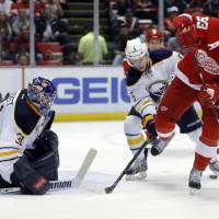 Photo - Detroit Red Wings' Johan Franzen (93), of Sweden, tries a back-hand pass against Buffalo Sabres' Chad Ruhwedel (5) while in front of Buffalo Sabres goalie Matt Hackett (31) during the second period of an NHL hockey game Friday, April 4, 2014, in Detroit. (AP Photo/Duane Burleson)