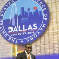 Photo - Former Dallas Cowboys player Michael Irvin walks on stage to participate in a panel discussion on race and sports at the U.S. Conference of Mayors meeting Monday, June 23, 2014, in Dallas. (AP Photo/LM Otero)