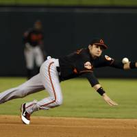 Photo -   Baltimore Orioles second baseman Ryan Flaherty can't stop a single by Texas Rangers' Michael Young during the fourth inning of an American League wild-card playoff baseball game Friday, Oct. 5, 2012 in Arlington, Texas. (AP Photo/Tony Gutierrez)