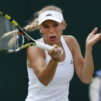 Photo - Caroline Wozniacki of Denmark plays a return to Barbora Zahlavova Strycova of the Czech Republic  during their women's singles  match at the All England Lawn Tennis Championships in Wimbledon, London, Monday, June 30, 2014. (AP Photo/Sang Tan)