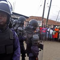 Photo - Liberia security forces dressed in riot gear, left, control a crowd of people in the West Point area, as the government clamps down on the movement of people to prevent the spread of the Ebola virus in Monrovia, Liberia, Wednesday, Aug. 20, 2014. Security forces deployed Wednesday to enforce a quarantine around a slum in the Liberian capital, stepping up the government's fight to stop the spread of Ebola and unnerving residents. (AP Photo/Abbas Dulleh)