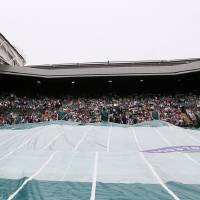 Photo - The covers go onto Centre Court as rain stopped play during a Women's second round singles match between Agnieszka Radwanska of Poland and Mathilde Johansson of France at the All England Lawn Tennis Championships in Wimbledon, London, Thursday, June 27, 2013. (AP Photo/Kirsty Wigglesworth)