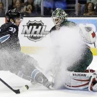 Photo - San Jose Sharks center Logan Couture (39) kicks up ice with his skates as he closes in on Minnesota Wild goalie Niklas Backstrom, of Finland, during the first period of an NHL hockey game in San Jose, Calif., Thursday, April 18, 2013. (AP Photo/Marcio Jose Sanchez)