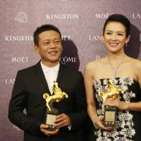 Photo - Best Leading Actor Lee Kang Sheng, left, and actress Zhang Ziyi hold their awards for their films