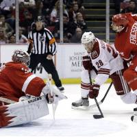 Photo - Detroit Red Wings goalie Jimmy Howard, left, stops a shot by Phoenix Coyotes center Lauri Korpikoski (28), of Finland, as Detroit Red Wings defenseman Jonathan Ericsson, of Sweden, defends in the first period of an NHL hockey game in Detroit, Monday April 22, 2013. (AP Photo/Paul Sancya)