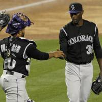 Photo - Colorado Rockies catcher Wilin Rosario (20) congratulates Rockies relief pitcher LaTroy Hawkins, right, to complete the save to defeat the Los Angeles Dodgers in eleven innings of a baseball game on Friday, April 25, 2014, in Los Angeles. (AP Photo/Alex Gallardo)