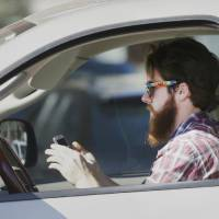 Photo - A man works his phone as he drives through traffic in Dallas. AP file photo