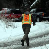 Photo - A man with King County Search and Rescue runs toward scene of avalanche at exit 47 along I-90 near Snoqualmie Pass, Sat. April 13, 2013. (Photo by Ken Lambert/The Seattle Times)  OUTS: SEATTLE OUT, USA TODAY OUT, MAGAZINES OUT, TELEVISION OUT, SALES OUT. MANDATORY CREDIT TO:  KEN LAMBERT / THE SEATTLE TIMES.