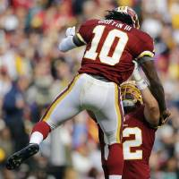 Photo -   Washington Redskins quarterback Robert Griffin III is picked up by tight end Logan Paulsen after Griffin threw a touchdown pass to wide receiver Aldrick Robinson during the first half of an NFL football game against the Philadelphia Eagles in Landover, Md., Sunday, Nov. 18, 2012. (AP Photo/Patrick Semansky)