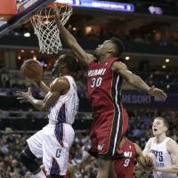 Photo - Charlotte Bobcats' Kemba Walker, left, drives past Miami Heat's Norris Cole (30) during the first half of an NBA basketball game in Charlotte, N.C., Saturday, Jan. 18, 2014. (AP Photo/Chuck Burton)