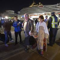 Photo - Passengers from the cruise ship Carnival Triumph are questioned by reporters after they disembarked in Mobile, Ala., Thursday, Feb. 14, 2013. The ship with more than 4,200 passengers and crew members has been idled for nearly a week in the Gulf of Mexico following an engine room fire. (AP Photo/John David Mercer)