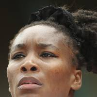 Photo - Venus Williams of the U.S. looks at the ball as she prepares to serve during the second round match of the French Open tennis tournament against at the Roland Garros stadium, in Paris, France, Wednesday, May 28, 2014. (AP Photo/David Vincent)